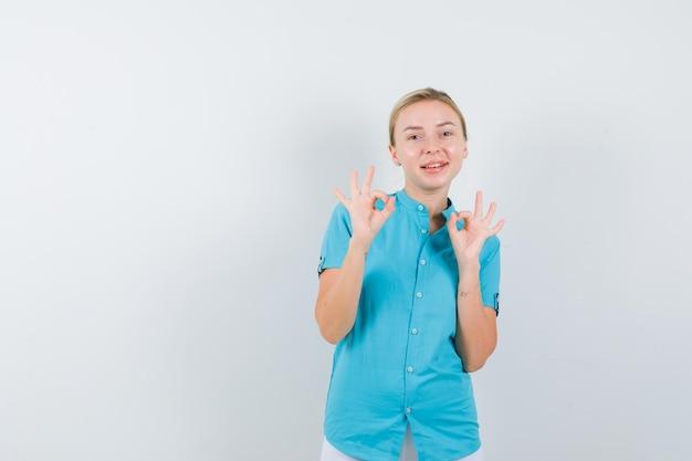 青いブラウスでokジェスチャーを示し、幸せな正面図を探している金髪の女性の肖像画