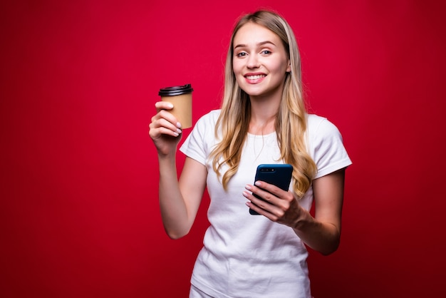 금발 여자의 초상화는 전화를 사용하고 붉은 벽에 테이크 아웃 커피를 들고