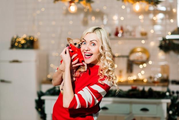 チワワ犬を保持しているクリスマスサンタを着ている金髪の女性の肖像画