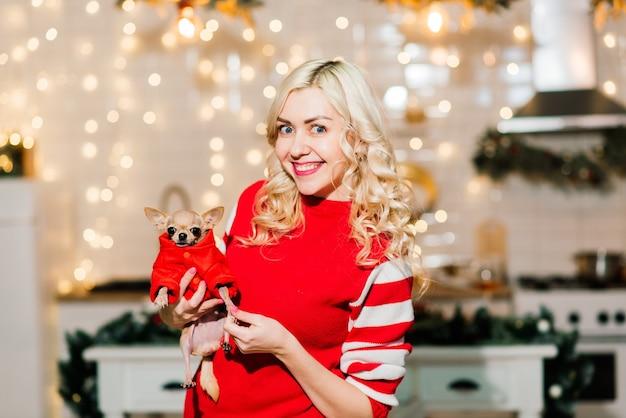 クリスマスの装飾が施されたキッチンでチワワの犬をクリスマスの衣装で保持し、笑顔でカメラを見てクリスマスサンタを着ている金髪の女性の肖像画。