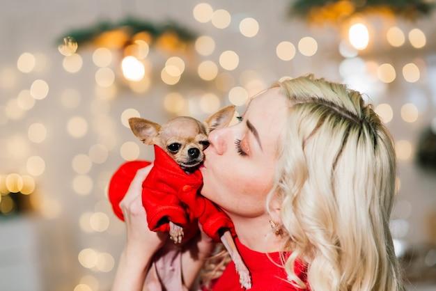 Портрет светловолосой женщины, носящей рождество санта, держа собак чихуахуа в рождественском костюме на кухне с рождественскими украшениями, улыбаясь и глядя в камеру.