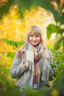 짧은 머리를 한 금발 여성의 초상화는 회색 양모 코트와 격자 무늬 스카프를 입고 숲을 걷는다
