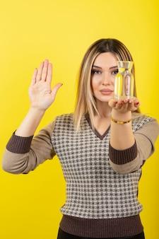黄色の上に立っている水のガラスを持つ金髪の女性の肖像画。
