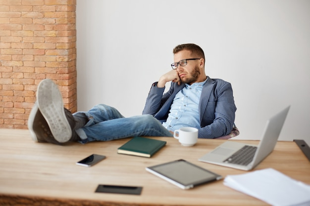 メガネと青いスーツの退屈な大人の白人のひげを剃っていない男性会社のマネージャーの肖像画は、オフィスでの長い一日の後に疲れて、不幸な表情でテーブルに足で座っています。