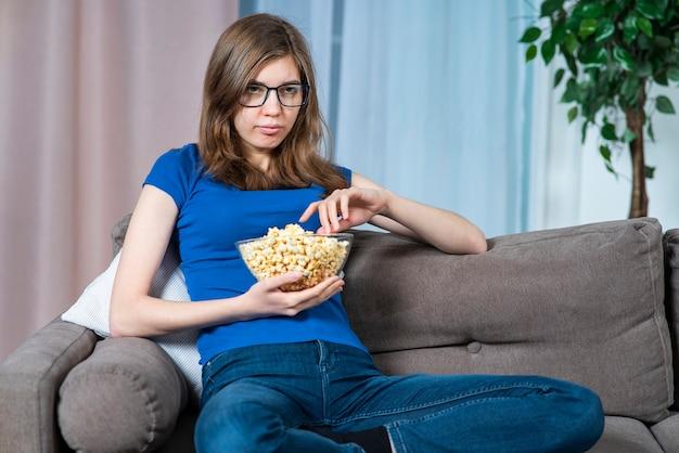Портрет скучающей девушки, молодой одинокой женщины в очках, сидящей на диване или софе дома, ест еду, попкорн, смотрит скучное телешоу, фильм, проводит время в одиночестве дома вечером в гостиной
