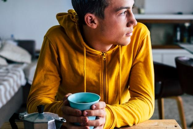 Портрет скучающего серьезного подростка-мужчины, завтракающего дома в одиночестве, глядя на улицу