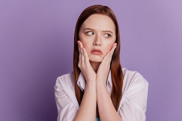 退屈な疲れた女性の手の頬の肖像画は、紫色の背景の横の空きスペースに見えます