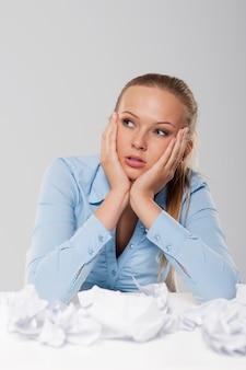 Портрет скучной блондинки-бизнес-леди с мятыми документами
