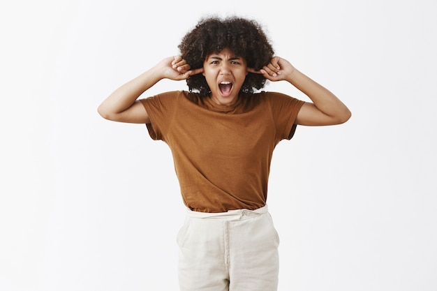 Портрет обеспокоенной и раздраженной недовольной несчастной афро-американской женщины с афро-прической, кричащей, закрыв уши указательными пальцами во время спора