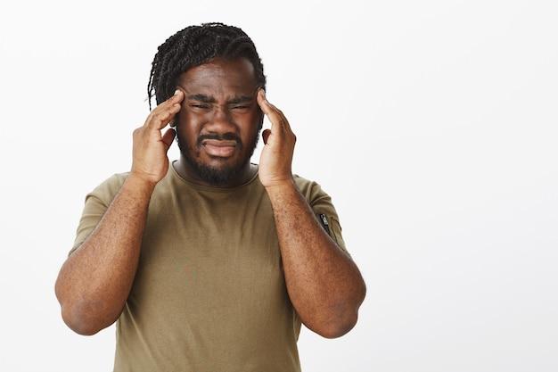 Портрет обеспокоенного парня в коричневой футболке, позирующего у белой стены