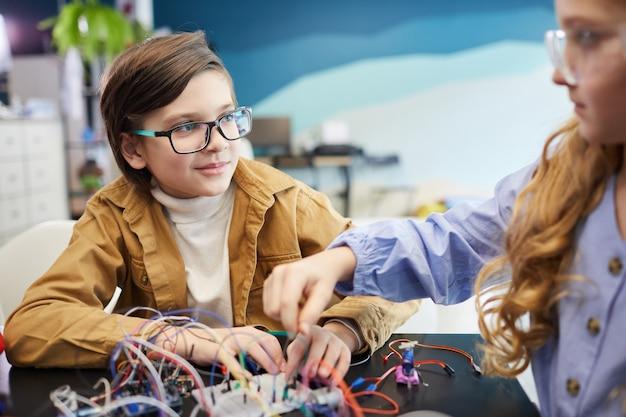 学校での工学の授業中にロボットを構築し、電気回路を実験する少年と少女の肖像画、コピースペース