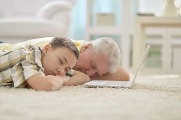 Портрет мальчика и деда, спящего возле ноутбука дома