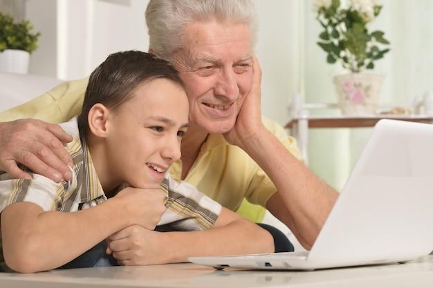 Портрет мальчика и деда с ноутбуком дома