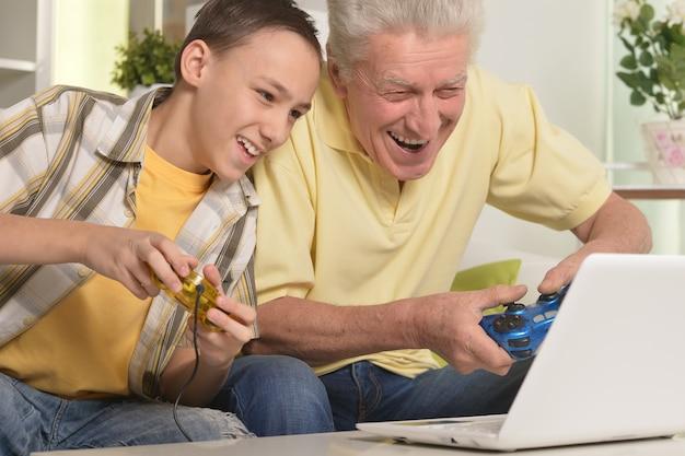 Портрет мальчика и деда с ноутбуком, играющих в компьютерную игру дома