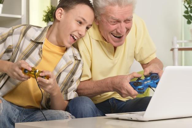 Портрет мальчика и деда с ноутбуком, играя в компьютерную игру дома