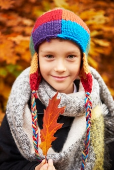 秋の葉を保持している少年の肖像画