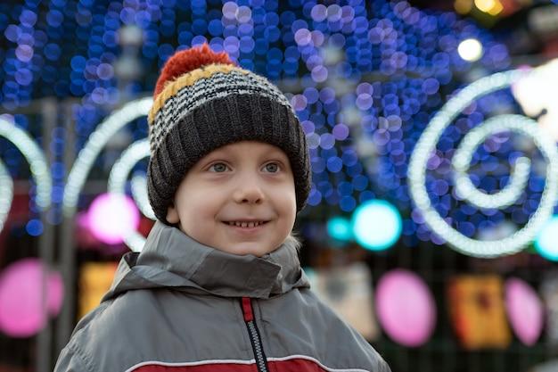 通りの新年の装飾を背景にニット帽をかぶった少年の肖像画。