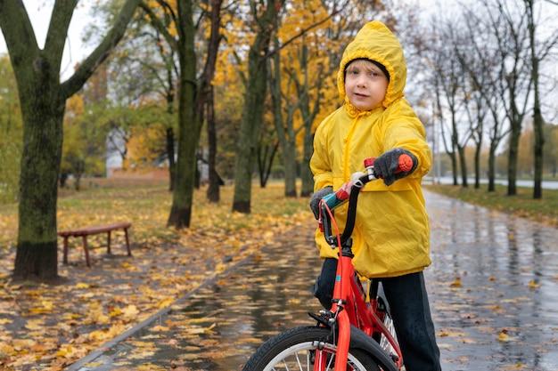 Портрет мальчика в желтом плаще на велосипеде на фоне осеннего парка. ребенок, езда на велосипеде под дождем.