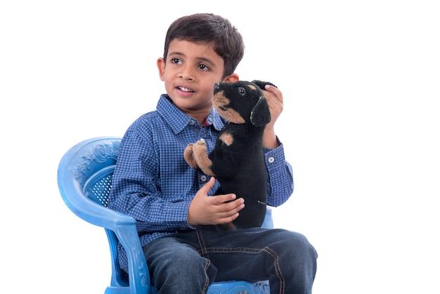 Портрет мальчика, играющего со своим домашним животным на белом фоне