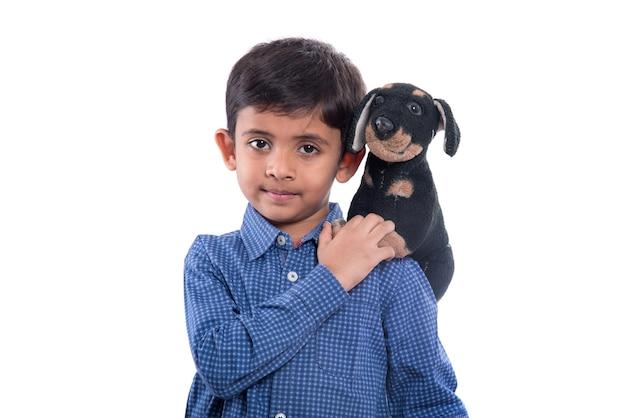 白い壁に彼のぬいぐるみペットと遊ぶ少年の肖像画