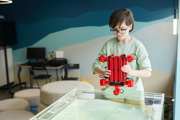 Портрет мальчика, опускающего роботизированную лодку в воду во время экспериментов с технологиями в лаборатории робототехники в школе, копия пространства