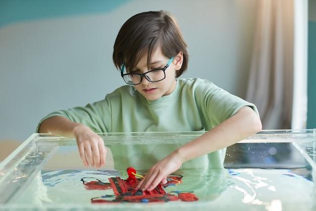 Портрет мальчика, опускающего роботизированную лодку в воду во время экспериментов с технологиями в лаборатории робототехники в школе
