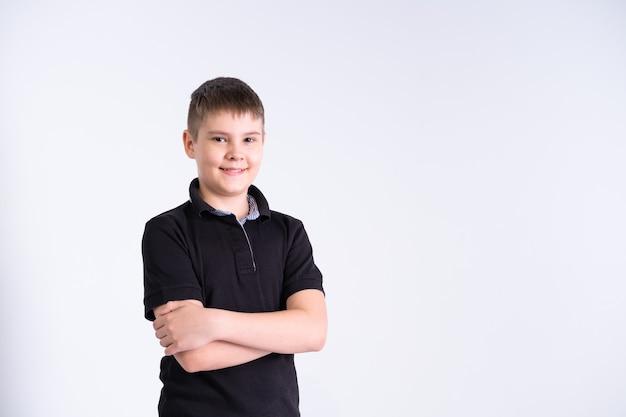 Портрет мальчика-подростка в черной футболке, смотрящего в камеру, улыбаясь с позитивным чувством на лице на белом фоне