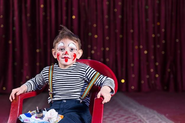 Портрет мальчика с макияжем клоуна, сидящего в красном пластиковом кресле с подносом для макияжа на сцене с красной занавеской, копией пространства справа