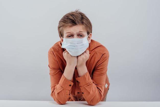 흰색 배경에 고립 된 의료 마스크와 소년의 초상화