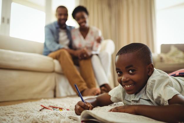 敷物の上に横たわっている間本に書いている少年のポートレート
