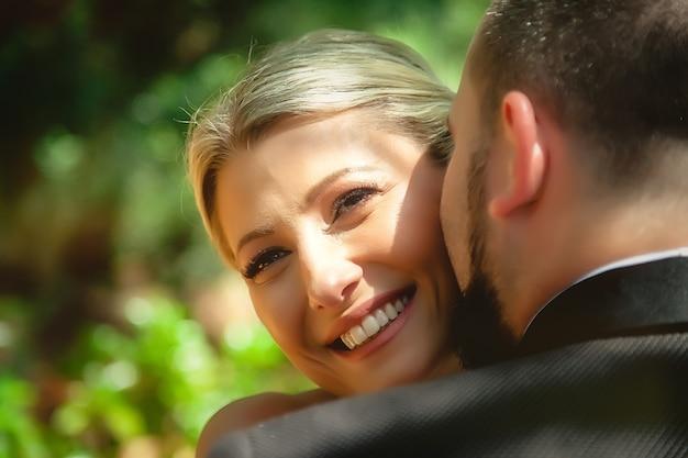 クローズアップで新郎新婦の肖像画。幸せな若い家族。男と女はお互いを愛しています。セレクティブフォーカス。対角線の画像。素晴らしい人たち。カップルは感情を示します。青い目をした金髪