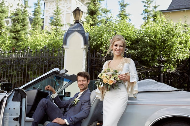 Портрет жениха и невесты, стоя возле ретро-автомобиля. свадьба