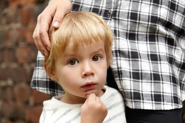 茶色の目の少年と彼の母親の肖像画。静かに立っているブロンドの髪を持つ5歳の子供。彼の愛するお母さんが近くに立ち、頭を撫でました。好奇心旺盛な表情。