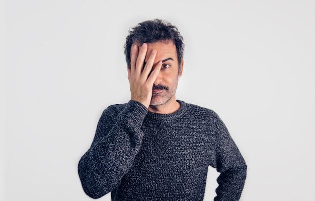 Портрет коричневого красивого мужчины с усами и серым свитером, выглядящего серьезным и разочарованным в камеру. серый фон.