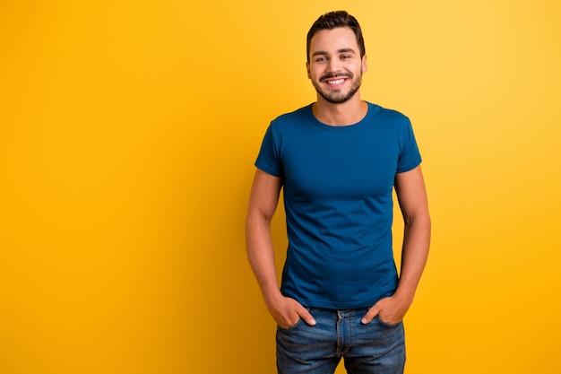 Портрет брюнетки парня, держась за руки в карманах