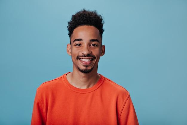 Портрет парня брюнет смотрит в камеру на синей стене