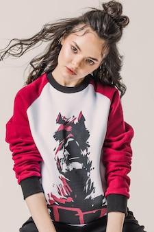 デアデビルプリントのスウェットシャツでポーズをとるブルネットの美しい少女の肖像画。