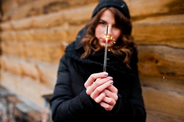 手にベンガルライトと黒のジャケット、帽子、スカーフのブルネットの巻き毛の女の子の肖像画。