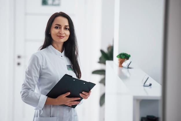클리닉 실내에 서 있는 손에 메모장을 들고 있는 갈색 머리 의사의 초상화.