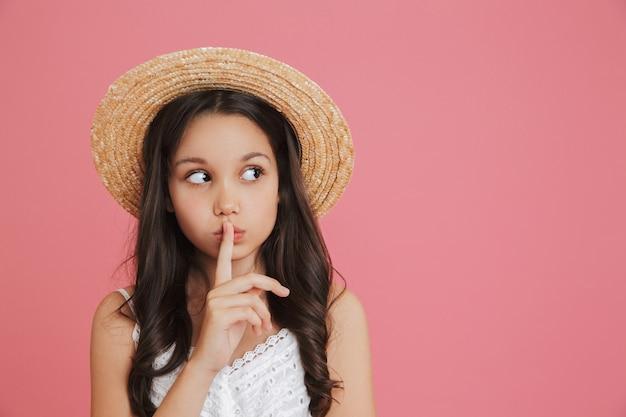 분홍색 배경 위에 절연 입술에 손가락을 잡고 copyspace에서 옆으로 찾고 흰 드레스와 밀짚 모자를 쓰고 갈색 머리 сгеу 소녀 8-10의 초상화