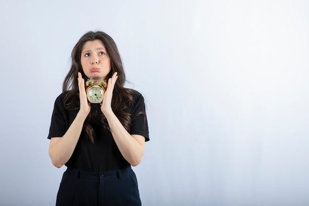 Портрет девушки брюнетки в черном обмундировании, держа часы на белой стене.