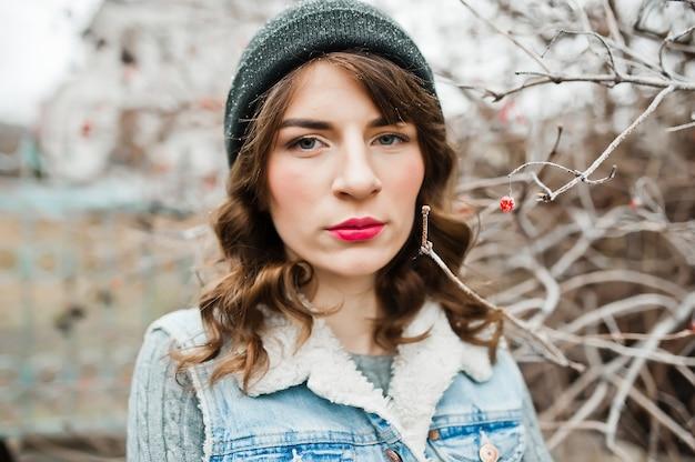 凍った茂みで帽子とジーンズのジャケットのブルネットの少女の肖像画。