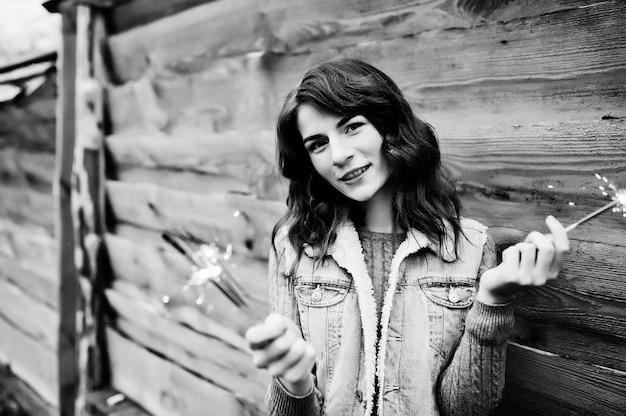 手にベンガルライトとジーンズジャケットのブルネットの少女の肖像画。