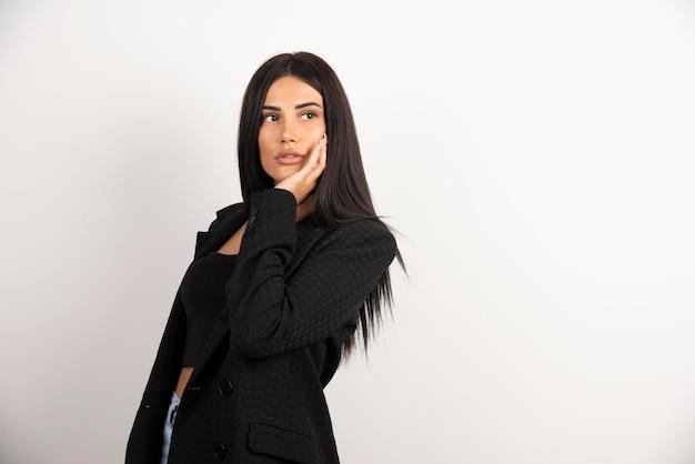 Портрет девушки брюнетки смотря ее сторону на белой предпосылке. фото высокого качества