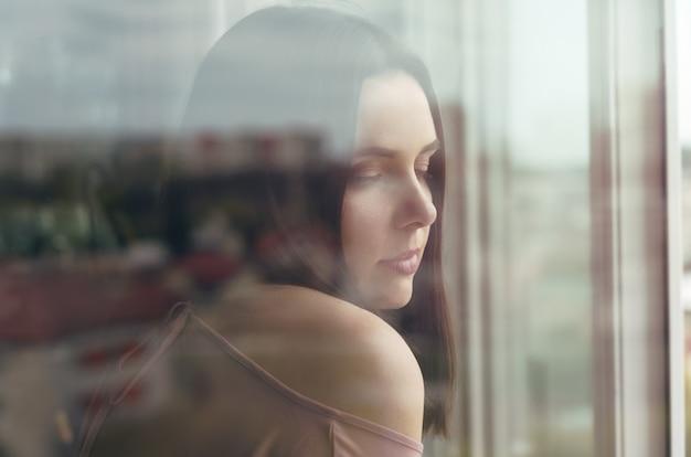 ガラスの都市反射と窓の後ろに立っているブルネットの少女の肖像画
