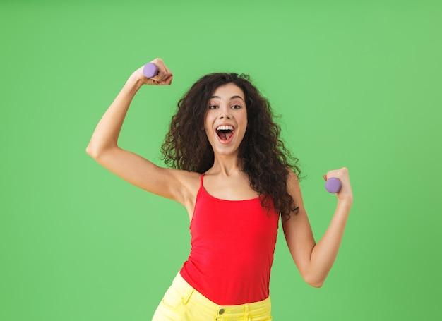 Портрет брюнетки в летней одежде, занимающейся спортом и поднимающей тяжести у зеленой стены
