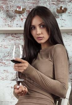 Портрет красивой девушки брюнетки, держащей бокал красного вина
