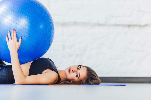 갈색 머리 예쁜 여자의 초상화, 그녀는 바닥에 파란색 피트니스 공을 가지고 누워있다