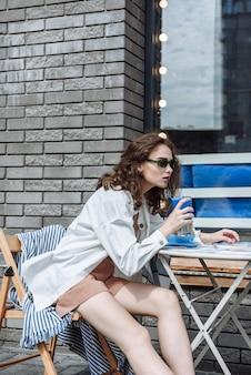 여름 레스토랑에서 칵테일을 마시는 갈색 머리 여자의 초상화