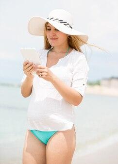 海でデジタル タブレットを使用して麦わら帽子のブルネットの女性の肖像画
